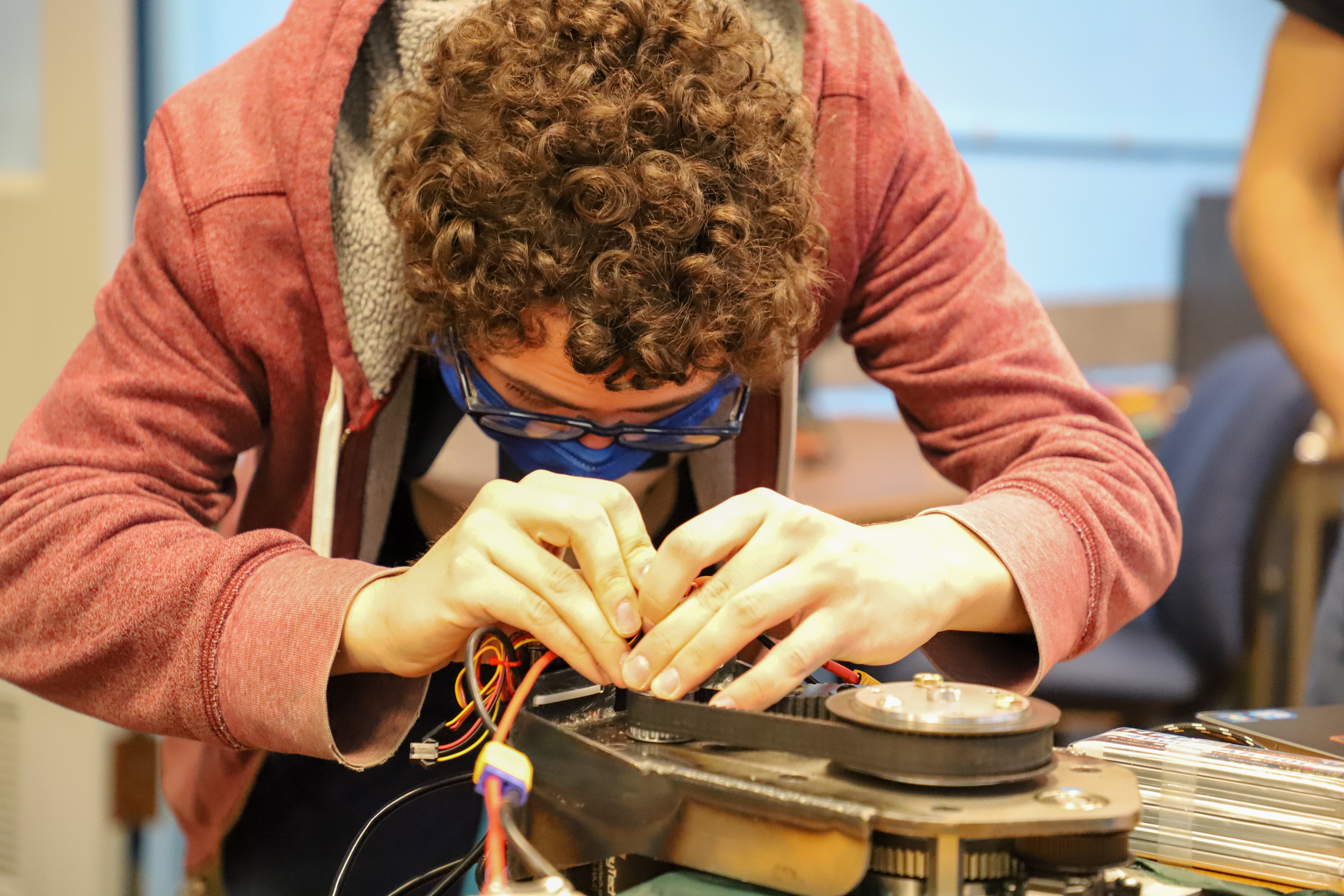 A Kettering University student works on the wiring of the robot's wheel.