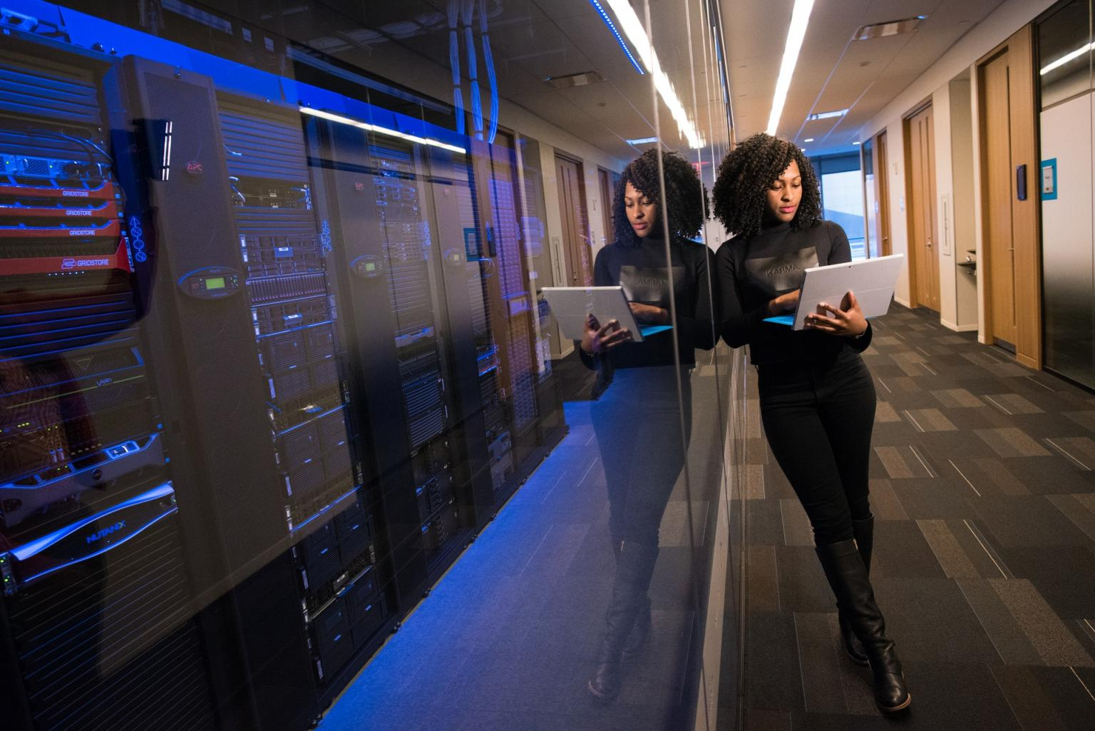 A data scientist stands outside a network systems room.