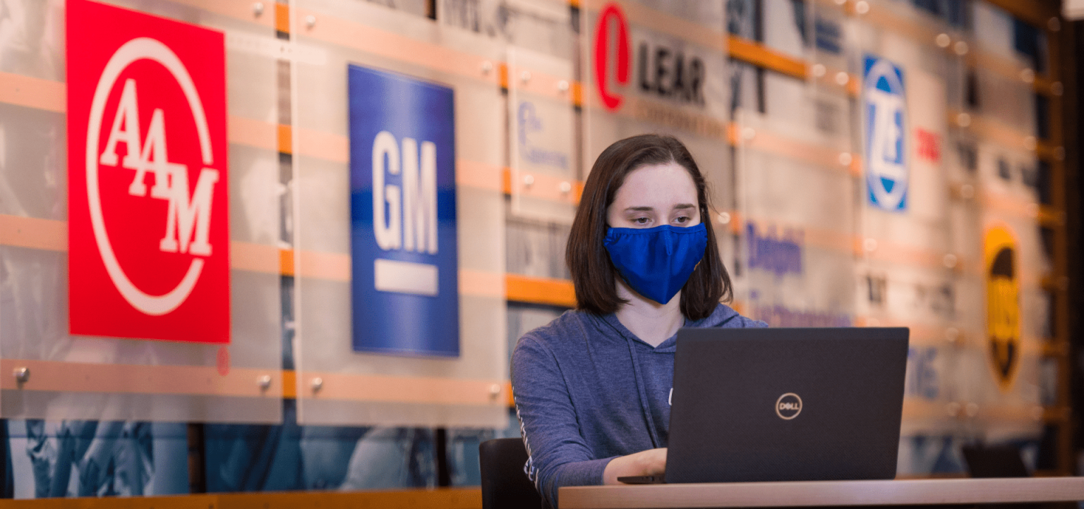 During the pandemic a student, wearing a face mask, works in the Great Court of the Campus Center in front of the employer wall.