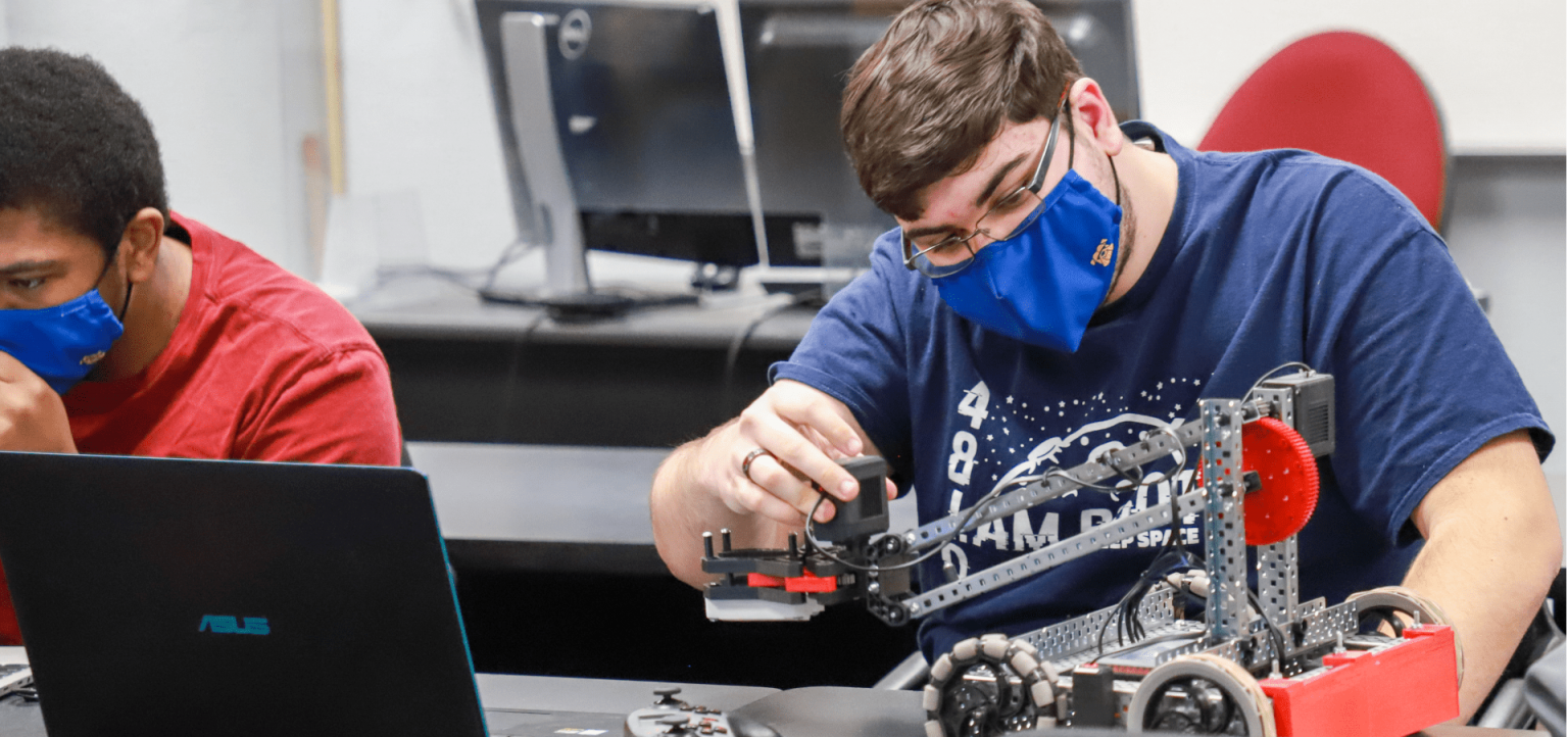 A students works on the mechanics of a robot in the VEX lab.