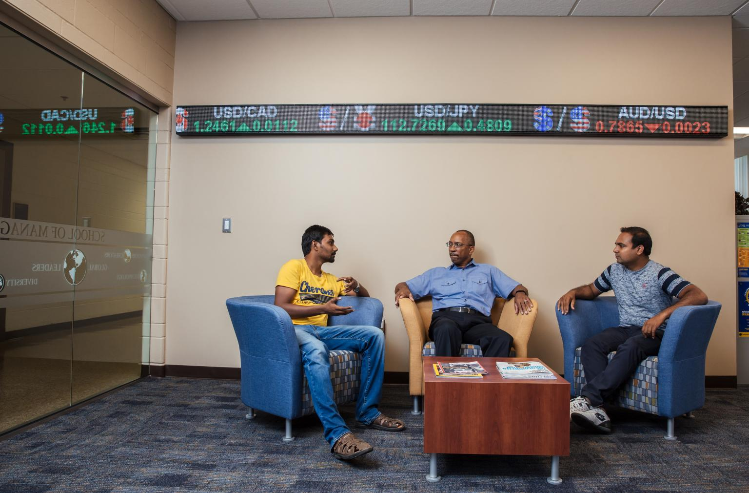 Graduate students discuss latest business trends with a faculty member in the School of Management.