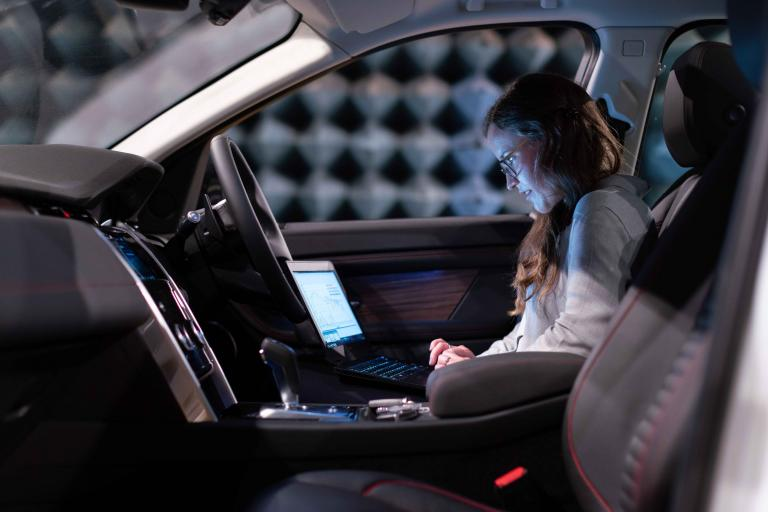 A woman inside a car with a laptop working
