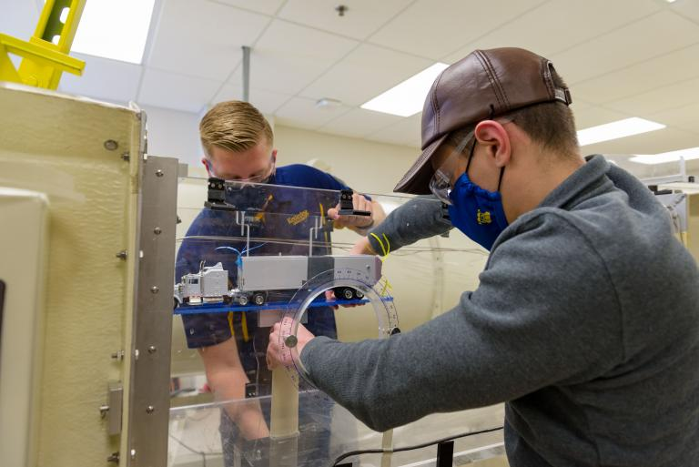Two Kettering University students work on a machine.