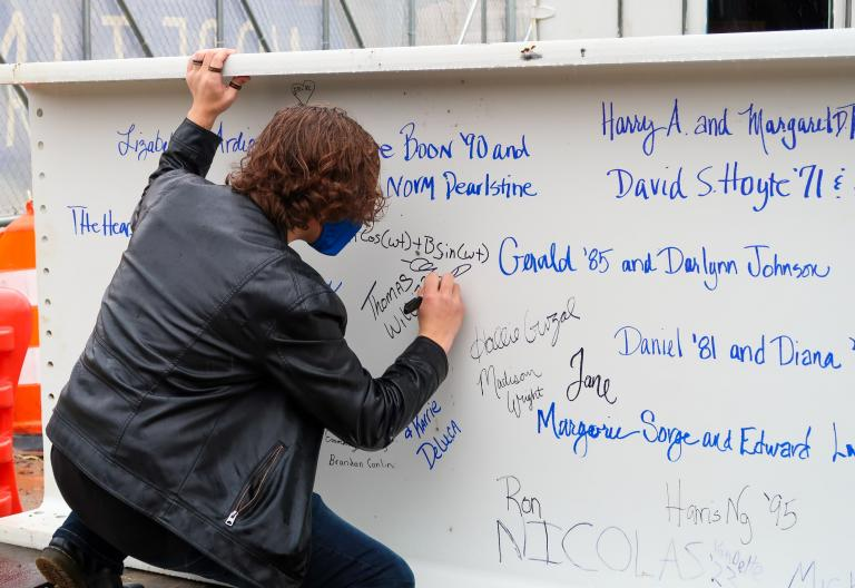 Student signing Learning Commons Beam