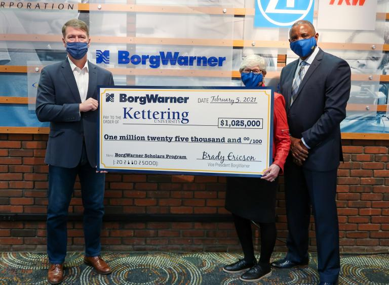 Two men and a woman posing with a large check from BorgWarner to Kettering University for $1,025,000