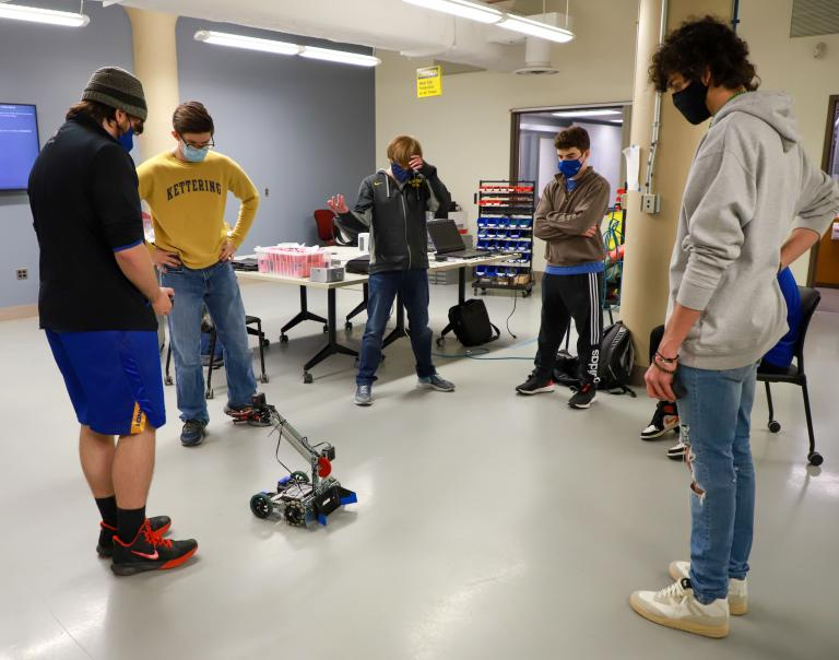 Kettering University students stand in a circle around a robot.