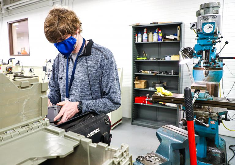 A masked Kettering University student works on piece of machinery.