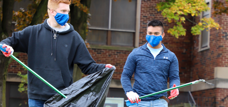 Two Kettering University students clean up trash in Flint.